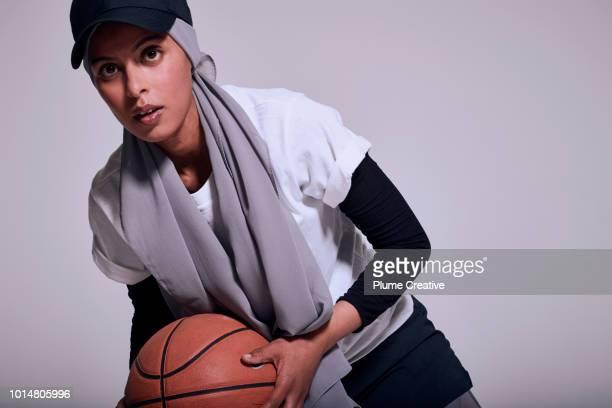 Muslim woman playing basketball in studio