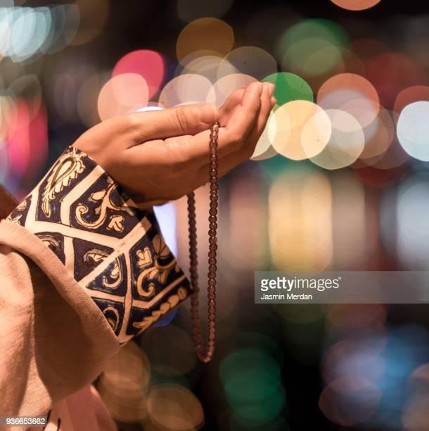 Muslim woman praying in city at night
