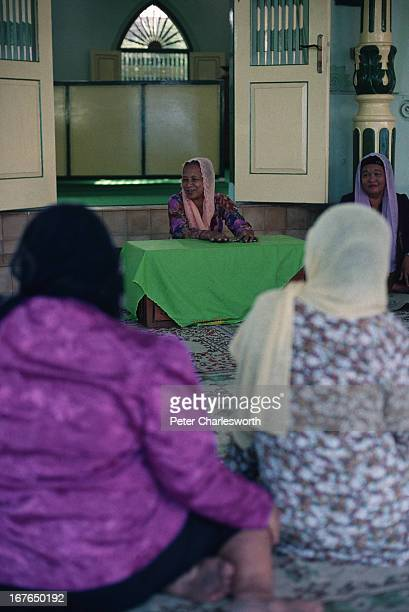 A muslim woman preacher preaches to fellow women followers of Islam outside the main doors of a small mosque after midday prayers In Southeast Asia...