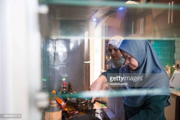muslim woman preparing a meal - malay hijab stock photos and pictures
