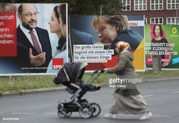 Muslim woman pushes a pram past election campaign billboards that show German Social Democrat chancellor candidate Martin Schulz German Chancellor...