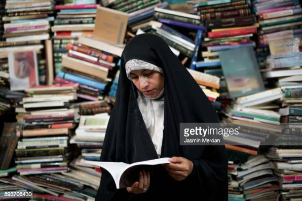 Muslim woman reading book in open book store