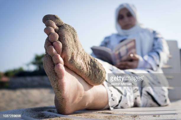 muslim woman relaxing on beach - arab feet photos et images de collection
