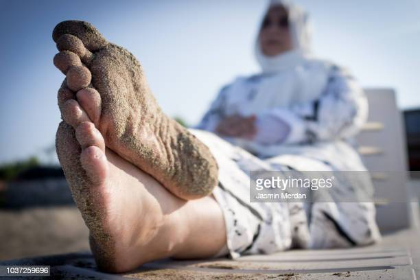 muslim woman relaxing on beach - hijab feet stock pictures, royalty-free photos & images