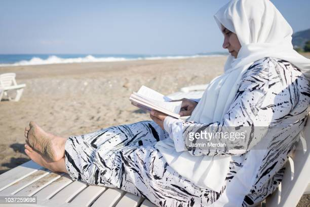 muslim woman relaxing on beach - hijab feet stock photos and pictures