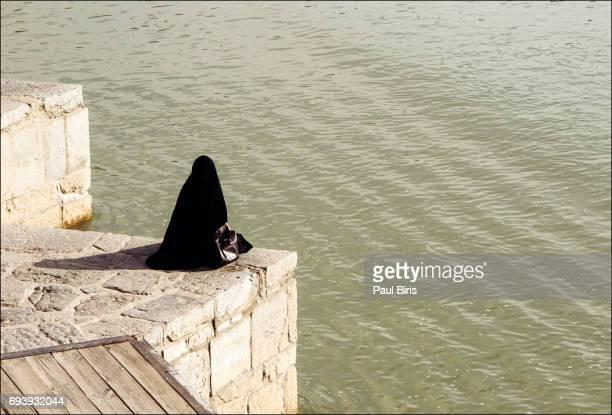 muslim woman resting on the khaju bridge on the zayandeh river, isfahan, iran - ザーヤンド川 ストックフォトと画像