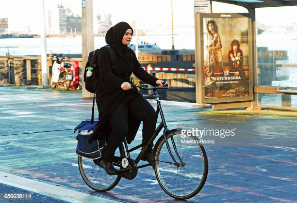 muslim woman riding a bicycle. - religion stock pictures, royalty-free photos & images