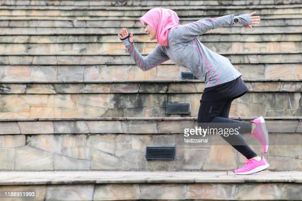 a muslim woman runner running at an amphitheatre - sprinting stock pictures, royalty-free photos & images