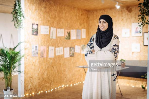 muslim woman runs small business - she is running the arts and craft shop - modest clothing stock pictures, royalty-free photos & images