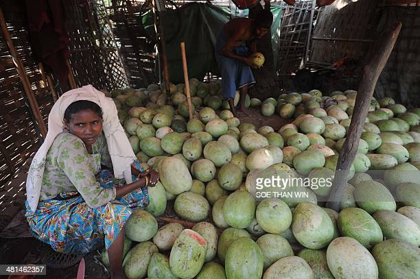 Muslim woman selling fruit waits for customers at a village on the outskirts of Sittwe in the western Myanmar state of Rakhine on March 30, 2014....