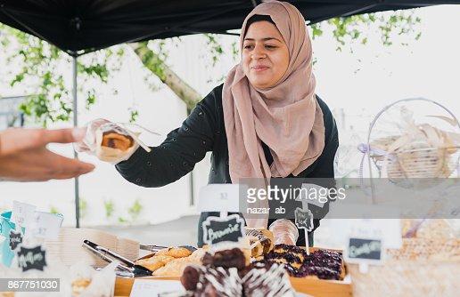 Muslim woman serving customer.