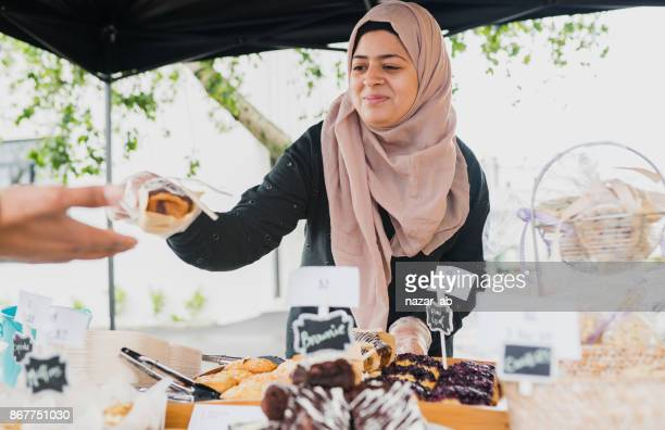 Muslim woman serving customer.
