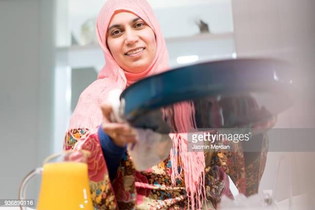 Muslim woman serving food at home