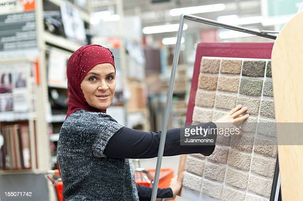 muslim woman shopping for carpet - moroccan culture stock photos and pictures