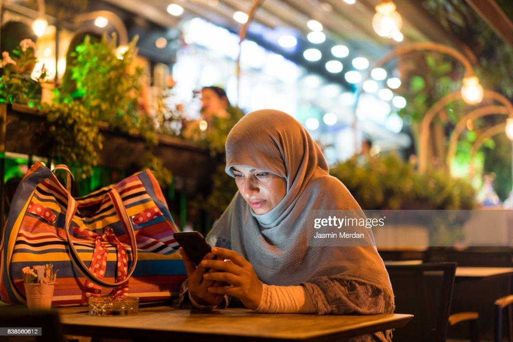 Muslim woman sitting alone using phone : Stock Photo