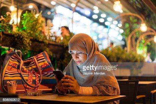 Muslim woman sitting alone using phone