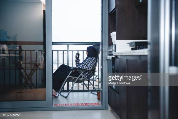 muslim woman sitting at balcoly - coronavirus uae stock pictures, royalty-free photos & images