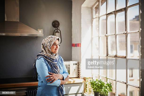 A muslim woman smiles whilst looking out of window