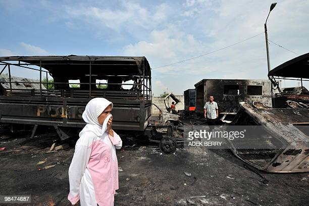 Muslim woman stands among damaged cars in Jakarta on 15, April 2010 following the clash between protesters and members of the security forces. Two...
