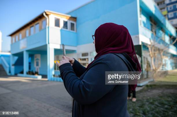 Muslim woman stands in front of the Muslim cultural center and mosque following a recent attack just before the beginning of the visit of Aydan...