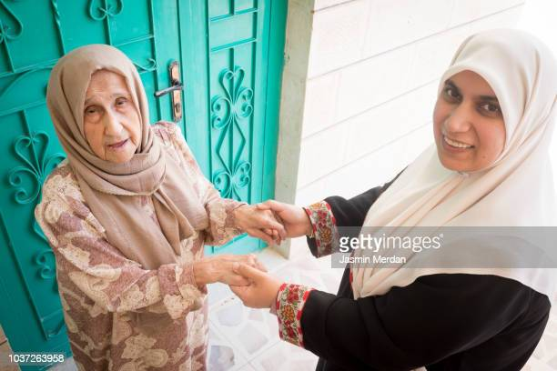 Muslim woman taking care of elderly mother