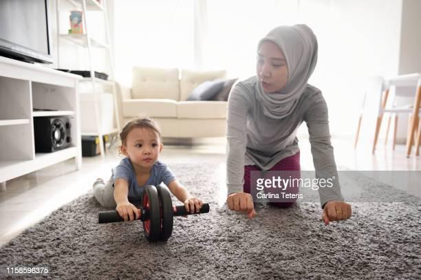 muslim woman teaching her young daughter to do excersise - zurückhaltende kleidung stock-fotos und bilder
