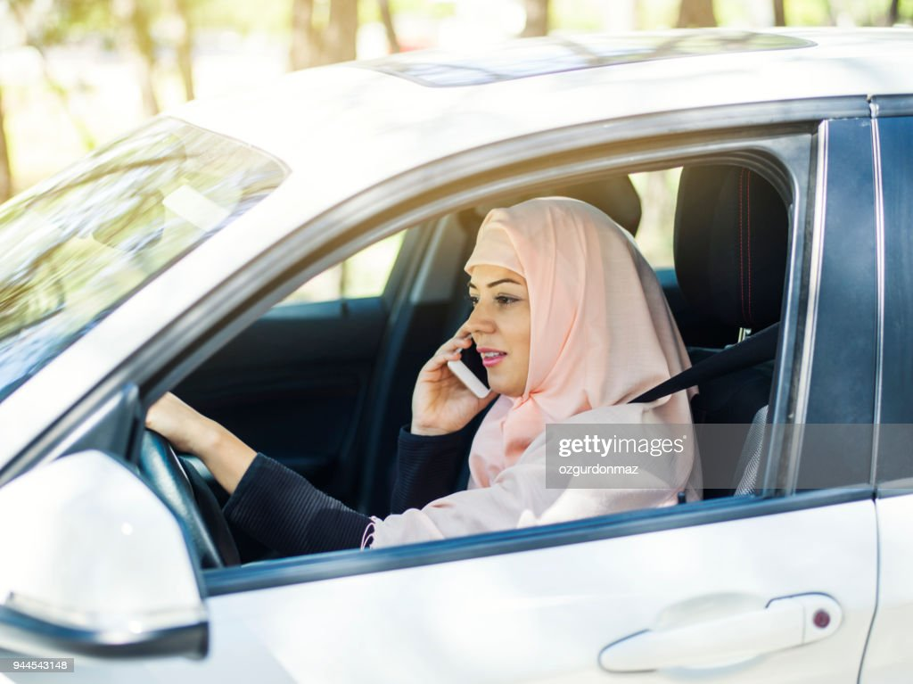 Muslim woman using smart phone while driving car : Stock Photo