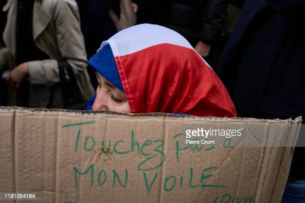 Muslim woman veiled with a French flag hold a banner reading Don't Touch My Veil as an estimated of ten thousand French citizens march from Gare du...