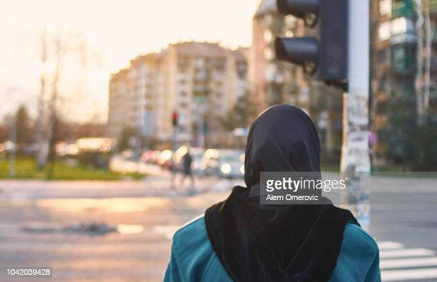 muslim woman waiting green light to cross the street - 宗教的なベール ストックフォトと画像