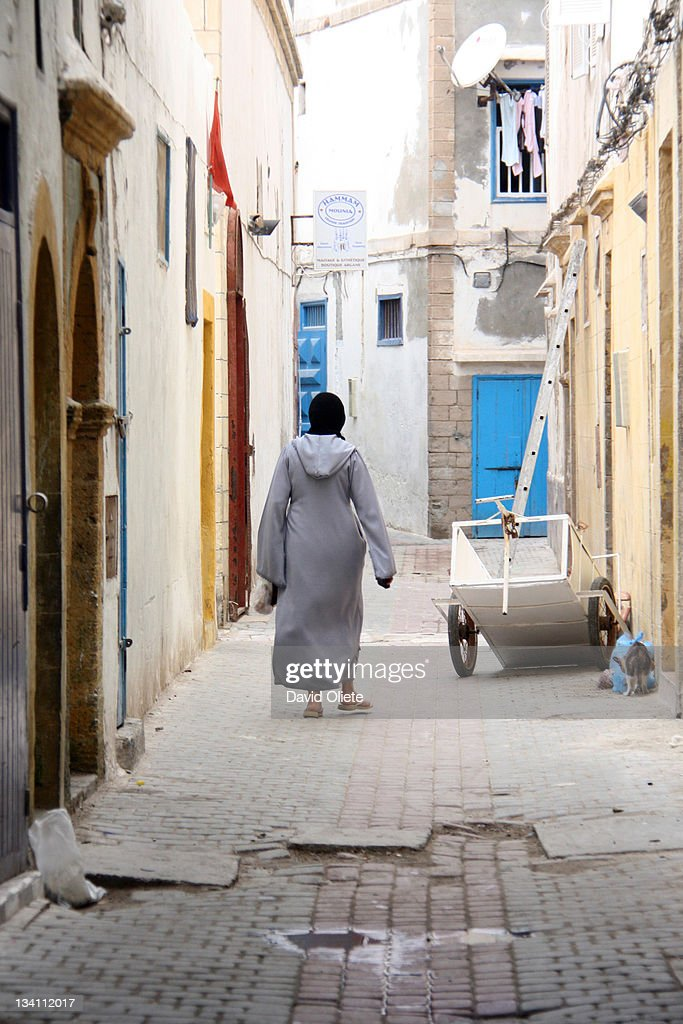 Muslim woman walking in narrow street : ストックフォト