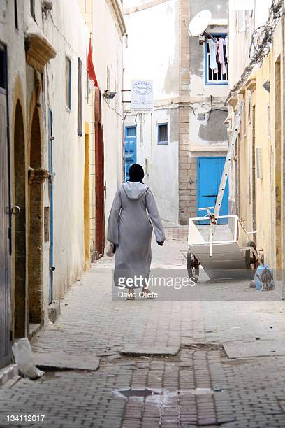 muslim woman walking in narrow street - david oliete stockfoto's en -beelden