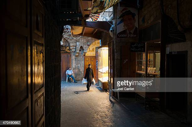 muslim woman walking past jewelry shops in tripoli, lebanon - lebanese ethnicity stock photos and pictures