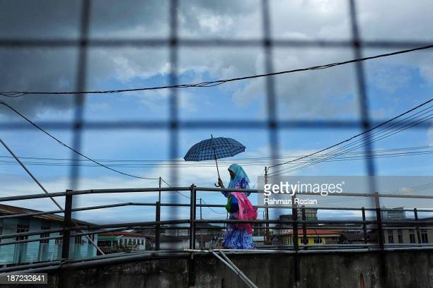 A muslim woman walks across a bridge at Kampung Air on November 7 2013 in Bandar Seri Begawan Brunei Darussalam Sultan Hassanal Bolkiah has announced...