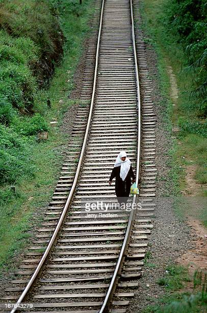 Muslim woman walks along the train tracks through the hilltop town of Haputale The tracks offer the easiest connections between different parts of...