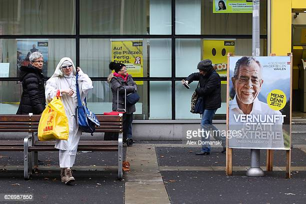 A muslim woman walks close to a election campaign posters for independent candidate Alexander von der Bellen on the street on December 1 2016 in...