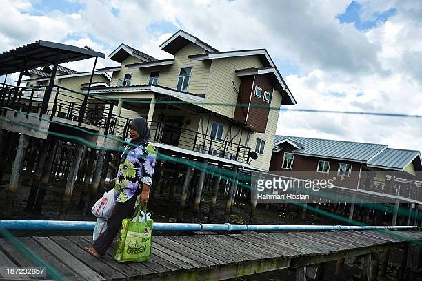 A muslim woman walks past a newly built government house at Kampung Air on November 7 2013 in Bandar Seri Begawan Brunei Darussalam Sultan Hassanal...