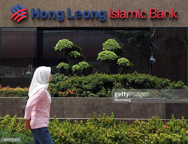 A Muslim woman walks past the headquarters of Hong Leong Islamic Bank in Kuala Lumpur Malaysia on Saturday Sept 25 2010 Primus Pacific Partners a...