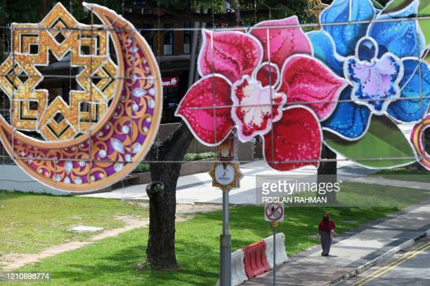 Muslim woman, wearing a face mask as a preventive measure against the spread of the COVID-19 novel coronavirus, walks past decorations for the holy...