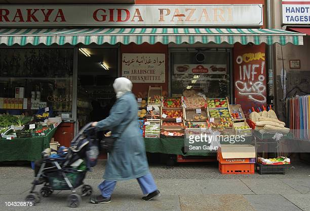 Muslim woman wearing a headscarf walks past a Turkish grocery store in the immigrantheavy district of Kreuzberg on September 21 2010 in Berlin...