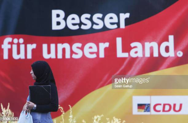 Muslim woman wearing a headscarf walks past an election campaign billboard by the opposition German Christian Democrats featuring a German flag and...