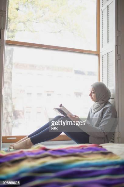 Muslim woman wearing a hijab reading on a window sill