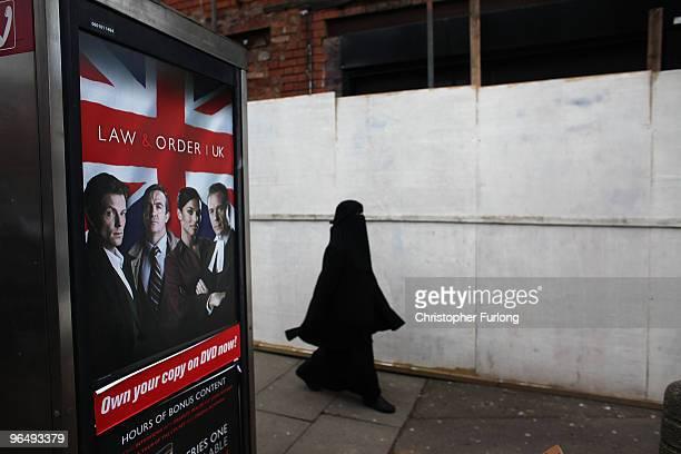 A muslim woman wearing a traditional burqa walks through the streets of Birmingham's Spark Hill area on January 27 2010 in Birmingham United Kingdom...