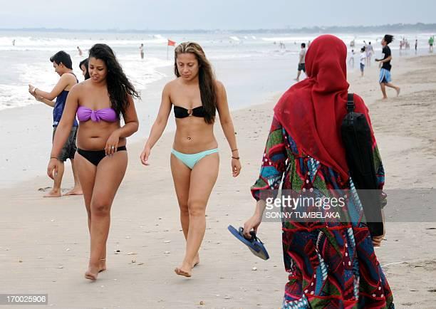 Muslim woman wearing a veil walks past foreign tourists wearing bikinis on Kuta beach near Denpasar on Indonesia's resort island of Bali on June 6,...