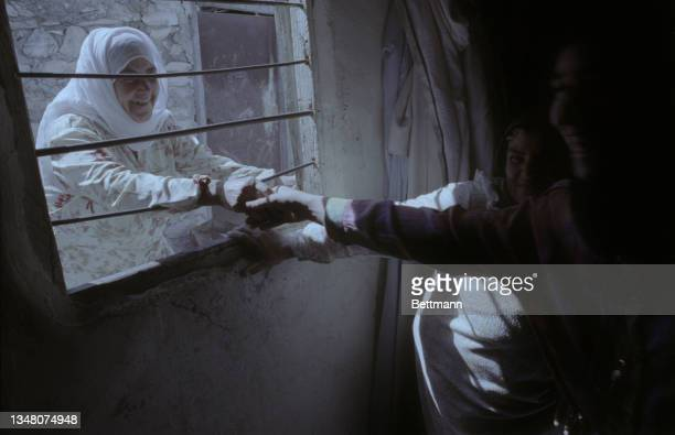 Muslim woman wearing a white hijab, smiling as she reaches through the bars over a window, holding the hands of those obscured by the darkness of the...