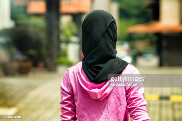 mujer musulmana llevar el hijab en la parte posterior de la zona residencial tiro - velo fotografías e imágenes de stock