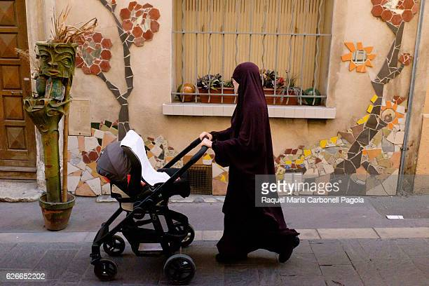 Muslim woman wearing niqab walking on street pushing baby cart
