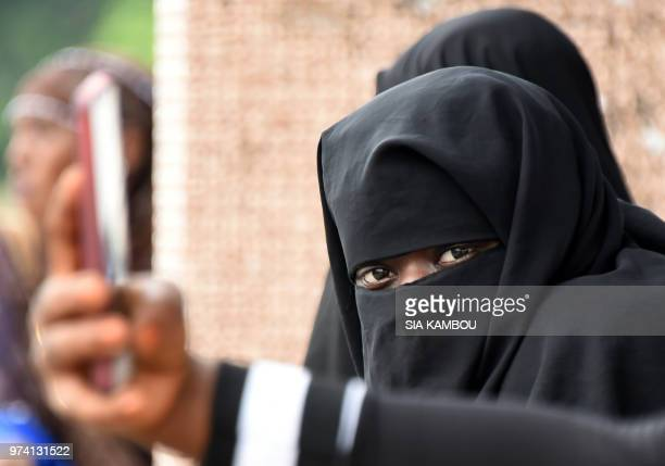 A Muslim woman wearing the niqab attends prayers at the site of a bus terminal in Adjame a quarter of Abidjan on June 14 as the Holy Month of Ramadan...