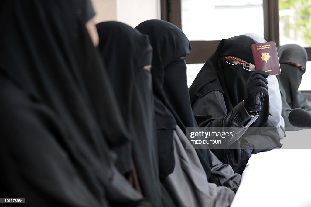 A Muslim woman wearing the niqab (veil which covers the body and leaves only a small strip for the eyes) shows her passport during a meeting with Imam Ali El Moujahed on May 18, 2010 in Montreuil, outside Paris. The French parliament unanimously adopted on May 11, 2010 a resolution condemning the full-face Islamic veil as an affront to the nation's values.