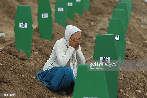 Muslim woman weeps at the fresh grave of one of 613 newly-identified victims of the 1995 Srebrenica massacre during a mass funeral attended by tens...