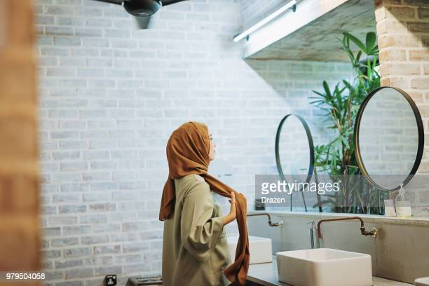 Muslim woman with fixing hijab in toilet